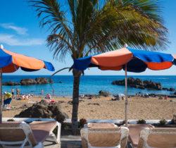 Hamacas con sombrillas ante Playa Chica - Puerto del Carmen, Tí